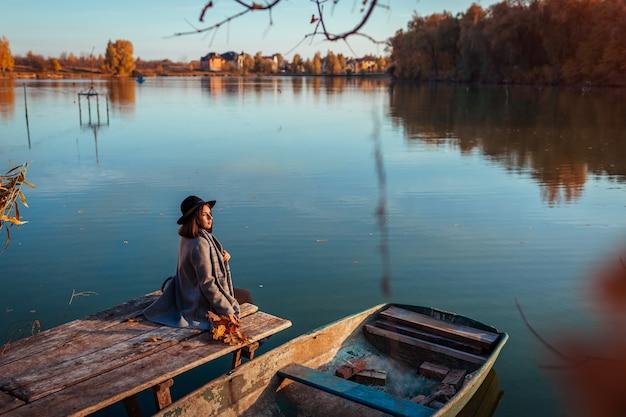 Mulher que senta-se no cais do lago pelo barco que admira a paisagem do outono. atividades da temporada de outono