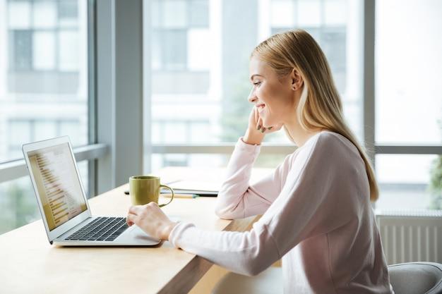 Mulher que senta-se no escritório que coworking ao usar o laptop.