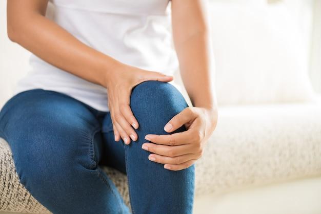 Mulher que senta-se no sofá e que sente a dor do joelho. conceito de saúde.