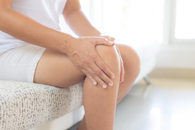 Mulher que senta-se no sofá e que sente a dor do joelho, conceito dos cuidados médicos.