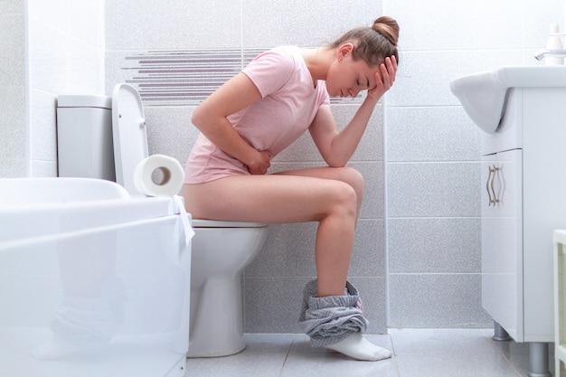 Mulher que sofre de diarréia, constipação e dor de estômago no banheiro. tratamento dor abdominal e intoxicação alimentar. cuidados de saúde