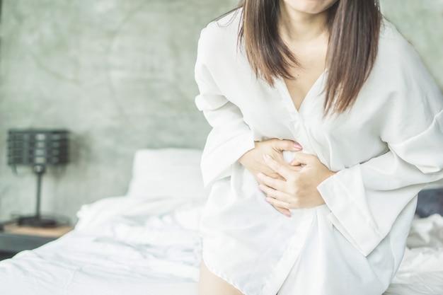 Mulher que sofre de dor de estômago durante o período