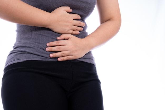Mulher que sofre de dor de estômago e branco isolado de lesão.