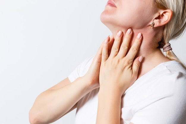 Mulher que sofre de dor de garganta.