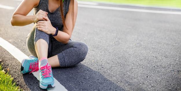 Mulher que sofre de dor no joelho enquanto corre no parque.