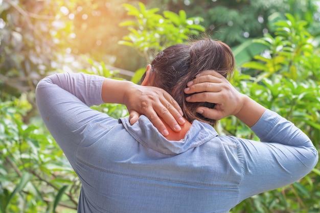 Mulher que sofre de dor no pescoço ao ar livre. conceito saudável