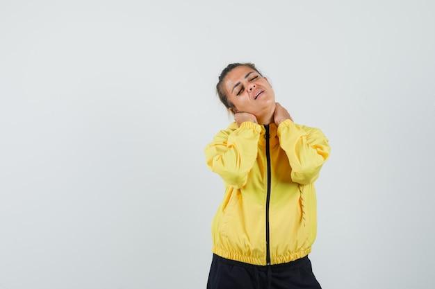 Mulher que sofre de dor no pescoço em um terno esporte e parece cansada, vista frontal.