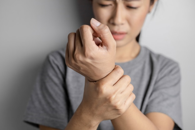 Mulher que sofre de dor no pulso.