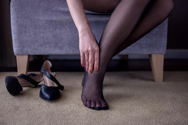 Mulher que sofre de dor no tornozelo ou pé