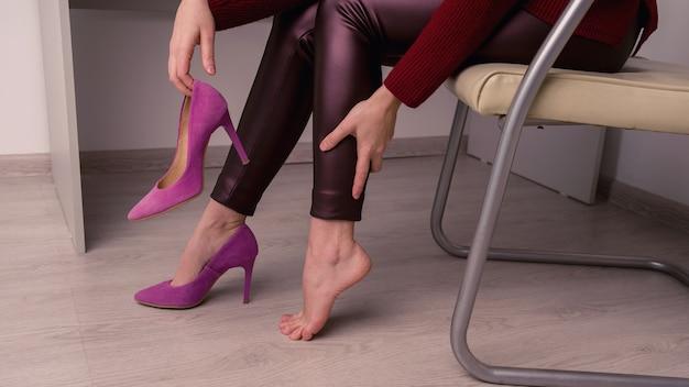 Mulher que sofre de dores nas pernas no escritório. ela esfregou calos terríveis em sapatos desconfortáveis de salto alto