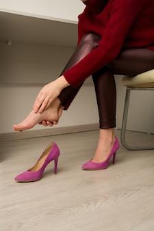 Mulher que sofre de dores nas pernas no escritório. ela esfregou calosidades terríveis em sapatos desconfortáveis de salto alto