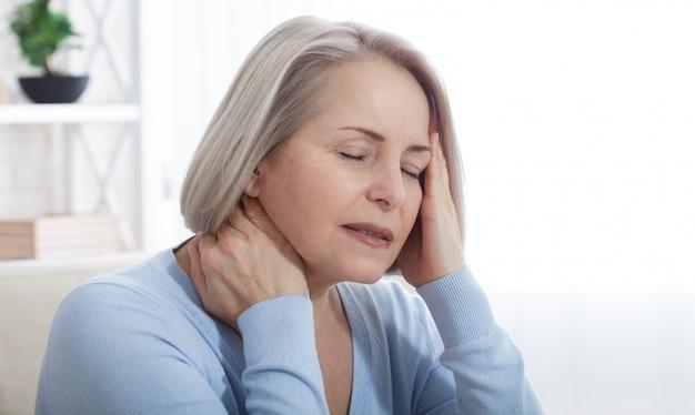 Mulher que sofre de estresse ou dor de cabeça fazendo careta de dor enquanto segura a parte de trás do pescoço