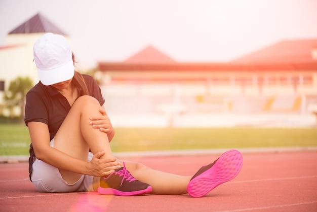 Mulher que sofre de uma lesão no tornozelo durante o exercício, cuidados de saúde e conceito do esporte.