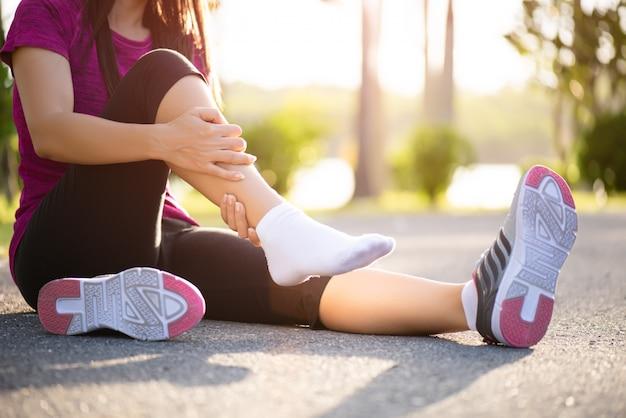 Mulher que sofre de uma lesão no tornozelo durante o exercício. cuidados de saúde e desporto.