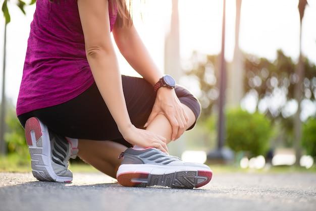 Mulher que sofre de uma lesão no tornozelo durante o exercício e correndo