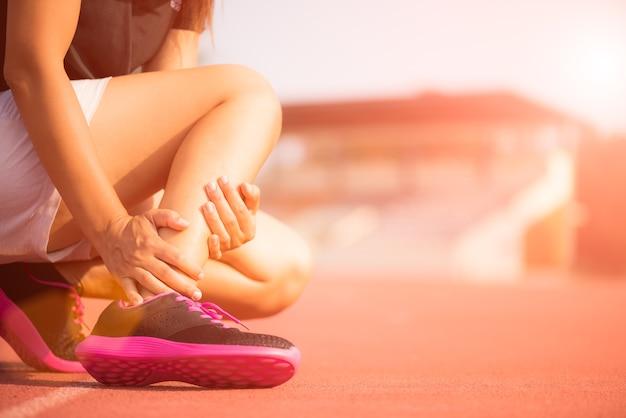 Mulher que sofre de uma lesão no tornozelo durante o exercício e correr na pista de atletismo.