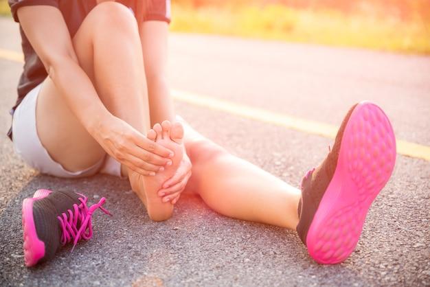 Mulher que sofre de uma lesão no tornozelo durante o exercício e corrida.