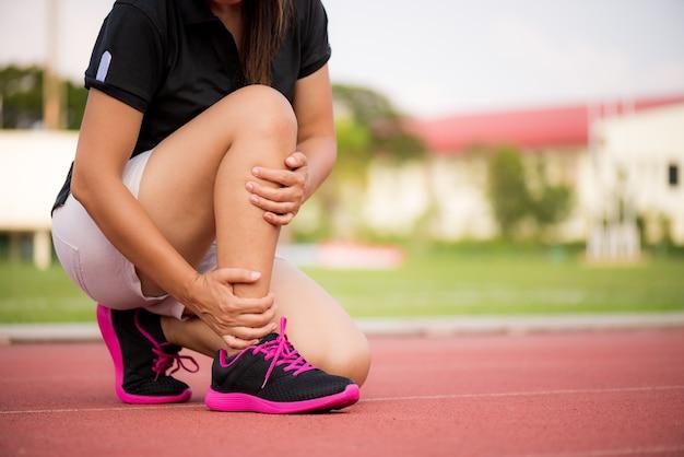 Mulher que sofre de uma lesão no tornozelo durante o exercício na pista de atletismo.