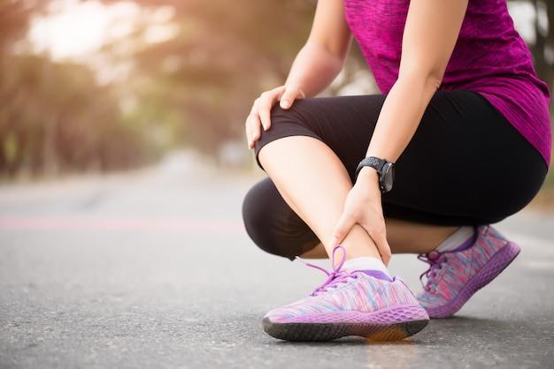 Mulher que sofre de uma lesão no tornozelo durante o exercício