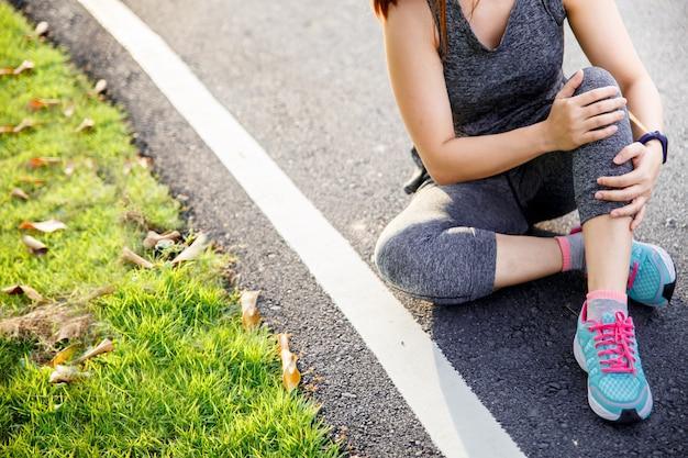 Mulher que sofre de uma perna dolorosa enquanto corre no parque.