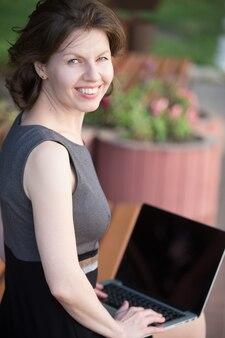 Mulher que sorri ao digitar em laptop