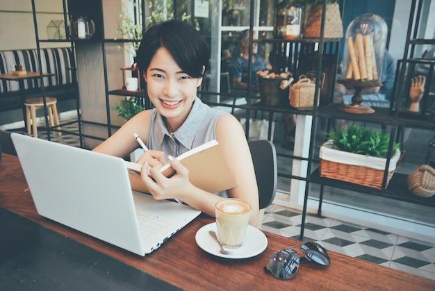 Mulher que sorri ao escrever numa agenda