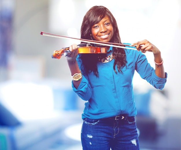 Mulher que sorri ao jogar um violino