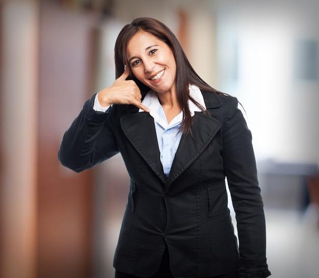 Mulher que sorri com a tomada de ação como ela chama ao telefone com a mão