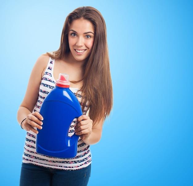 Mulher que sorri com um pote de detergente azul