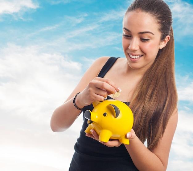 Mulher que sorri derramar uma moeda em um banco piggy