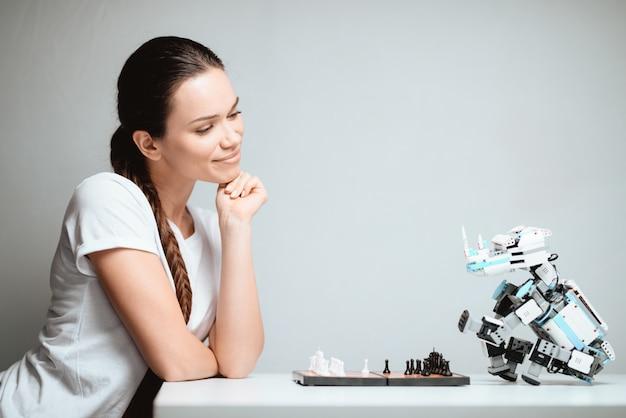 Mulher que sorri e joga a xadrez com robô.