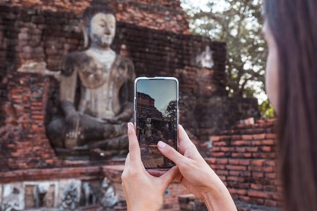Mulher que tira uma foto com o telefone em pé a imagem de buda de wat mahathat no parque nacional de sukhothai na tailândia.