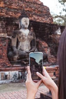 Mulher que tira uma foto vertical com o telefone de tela em pé buddha em wat mahathat no parque nacional de sukhothai.