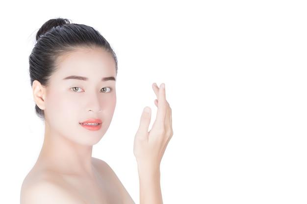Mulher que toca em sua cara, cosmetologia, beleza e termas, quando isolado no fundo branco.