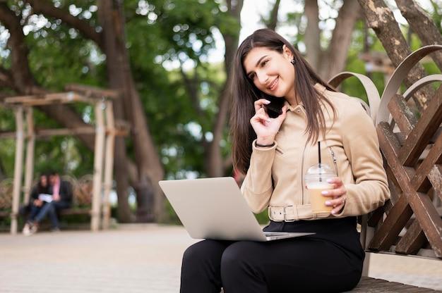 Mulher que trabalha ao ar livre enquanto toma uma bebida