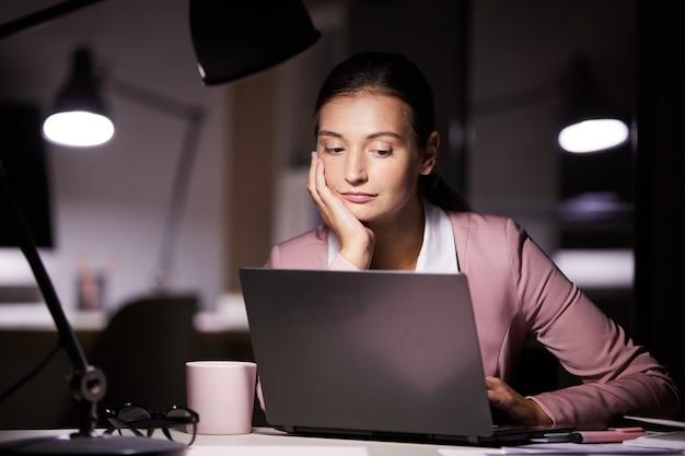 Mulher que trabalha até a noite no escritório