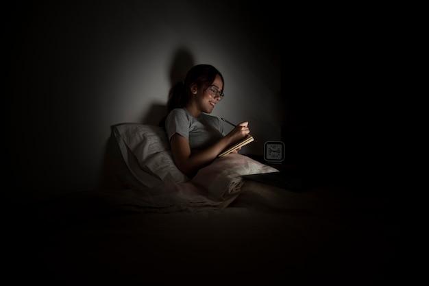 Mulher que trabalha até tarde em casa enquanto está na cama