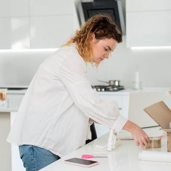 Mulher que trabalha com fita adesiva em casa