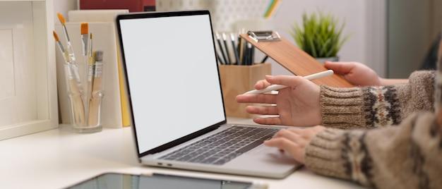Mulher que trabalha com laptop de mock-up e ferramentas de pintura durante um briefing com colegas