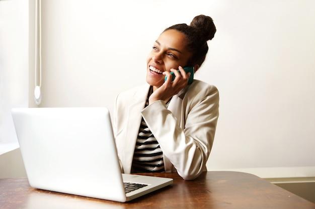 Mulher que trabalha com laptop e falando no celular