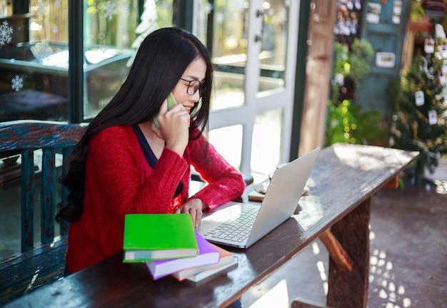 Mulher que trabalha com laptop e ligar com o celular no café