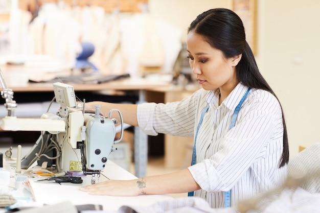 Mulher que trabalha com máquina de costura