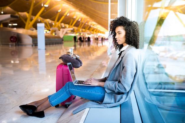 Mulher que trabalha com o laptop no aeroporto esperando na janela