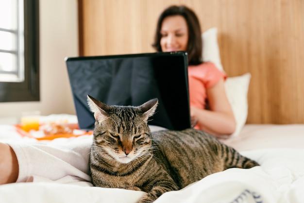 Mulher que trabalha com seu computador laptop e tomando café da manhã com seu gato na cama.