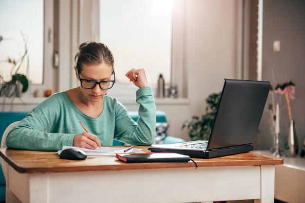 Mulher que trabalha em casa, escritório