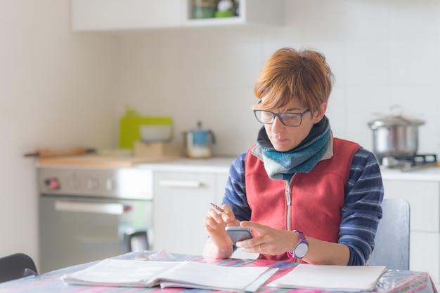 Mulher que trabalha em casa, leitura e escrita de documentos