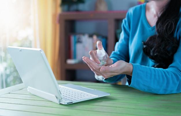 Mulher que trabalha em casa. limpando as mãos com gel desinfetante.