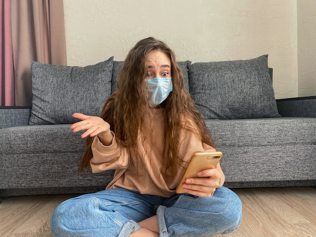 Mulher que trabalha em casa usa uma máscara médica protetora. o conceito de quarentena doméstica