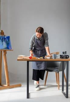 Mulher que trabalha em estúdio com pintura