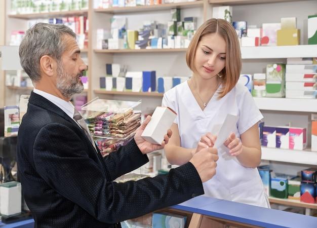 Mulher que trabalha em farmácia com cliente masculino.